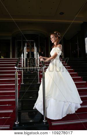 Wedding concept. Bride portrait in wedding dress on stairs