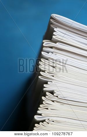 Stack of notebooks isolated on blue. Education and school concept