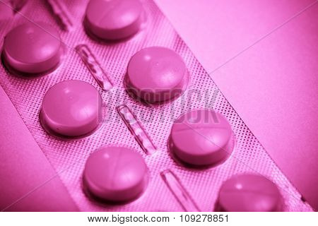 Pills on pink background. Medicine concept