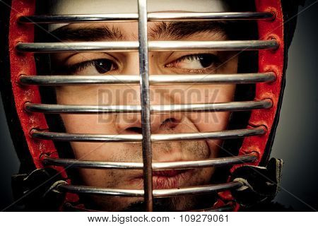 Face closeup in kedno helmet and eyes looking on side. Martial art concept portrait