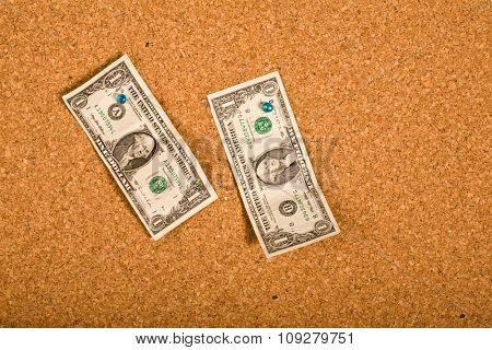 One dollar bills on a cork board with copy space. Money concept