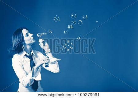 Woman making soap bubbles on blue background with copy space. Happy lifestyle concept