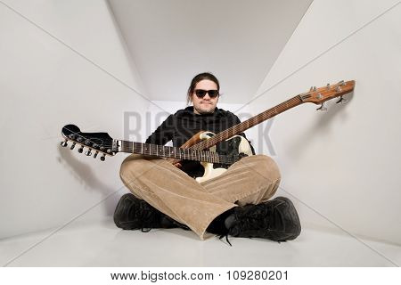 young man with guitar and bass in white tunnel space. Rock music concept