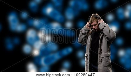 Handsome man in headphones enjoying the music. DJ in abstract sound space