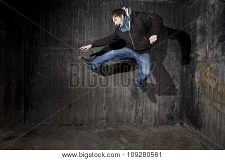 Man jumping in old black grungy room corner with shadows - breakdance concept