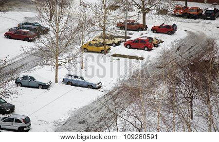 cars parked in parking lot with winter snow