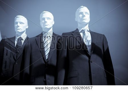 Mannequins in clothes store. Three men dolls in suits
