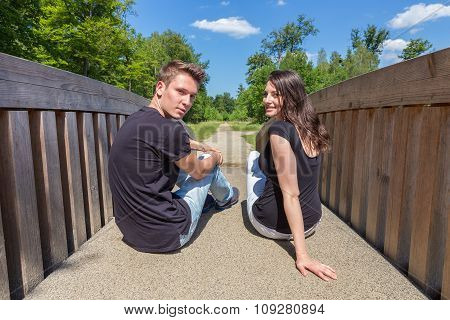 Young Attractive Dutch Couple Sitting On Wooden Bridge
