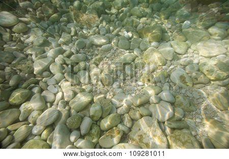 Pebble stones underwater on a sea bed. Marine background