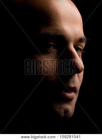 Shadow portrait in dark. Young bald man
