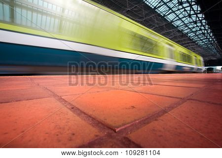 Commuter train in motion blur enters the city station