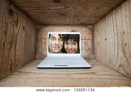 Two young man trapped inside laptop computer in old wooden box interior