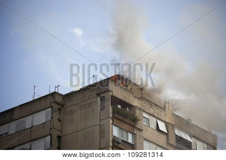 Fire on the roof of the the apartment building. Exploding particles flying