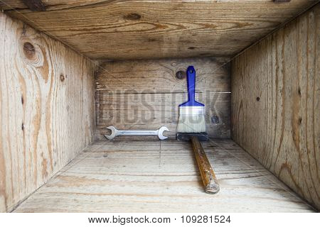 DIY home improvement tools in wooden box, hammer, wrench and paint brush