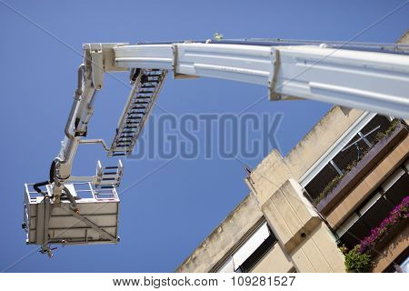 Mobile construction crane basket up in the sky reaching building top