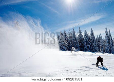 Man on snowboard making big splash of snow