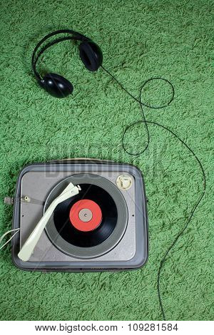 Headphones and  vintage turntable on green funky carpet