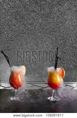 Alcoholic cocktails with dry ice smoke in front of broken glass background