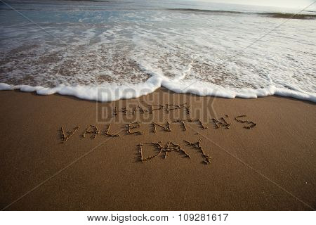 happy Valentine`s day  in sand on a beach with a wave coming