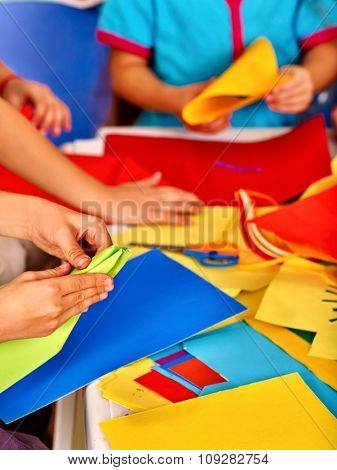 Group hands kids holding colored paper on table in kindergarten .