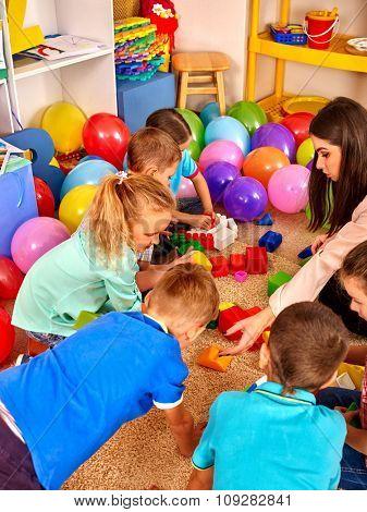Group children game blocks and other toy on floor in kindergarten . Top view.