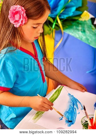 Beauty little girl with brush painting on table in  kindergarten .
