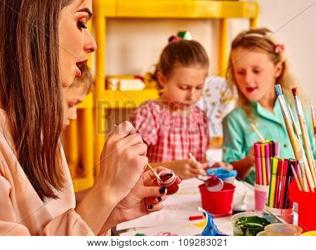 Children with teacher woman painting on paper at table  in  kindergarten . Four people.