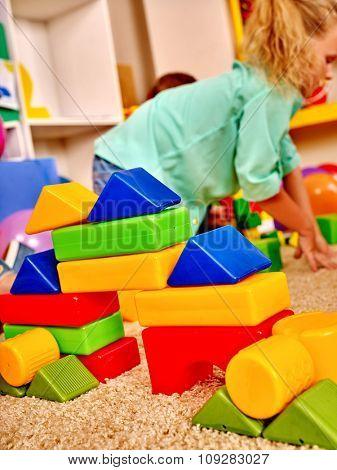 Girl game blocks on floor in kindergarten . Top view.