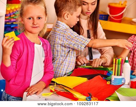 Group kids holding colored paper on table in kindergarten . Look at camera.