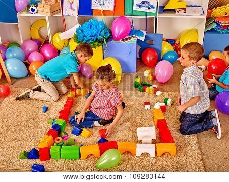 Group children male and female game blocks on floor in kindergarten . Top view.