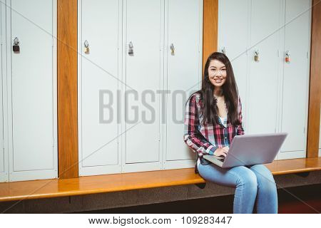 Smiling student sitting at the computer at the university