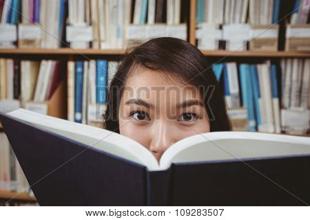Pretty student hiding face behind a book at the university