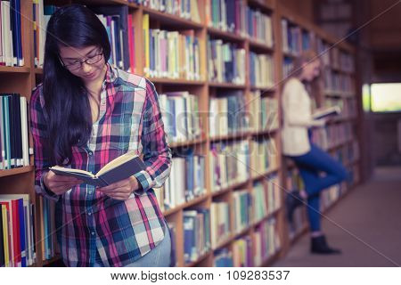 Smiling student leaning against bookshelves reading book at the university