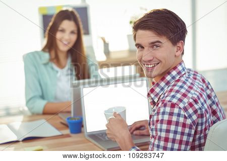 Creative team working together at desk in casual office