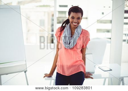 Smiling creative businesswoman by her desk in casual office