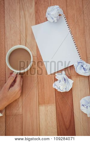 Cropped image of woman holding coffee cup in her office
