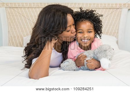 Mother kissing her smiling daughter on bed at home