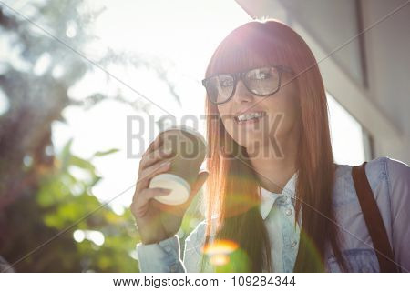 Smiing woman holding a cup of coffee outside