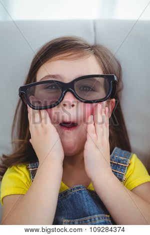 Close up of a girl wearing 3d glasses for a moive on the couch
