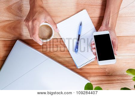 Overhead of feminine hands holding coffee and smartphone with notebook and laptop on table
