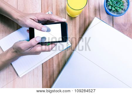 Overhead of feminine hands using smartphone with notebook, laptop and orange juice on table