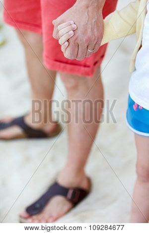 Close up of father and daughter holding hands