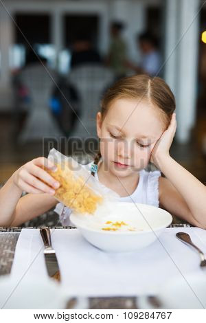 Adorable little girl eating cereal with milk for breakfast in restaurant