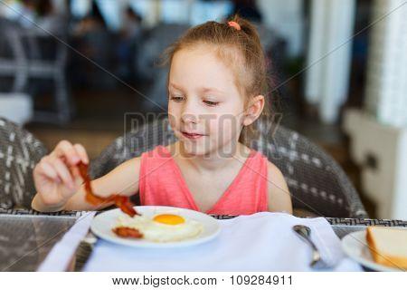Adorable little girl eating fried egg for a breakfast in restaurant