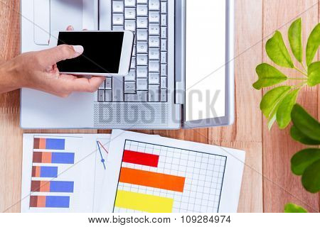 Overhead of businesswoman hands using smartphone with laptop and graphics on desk