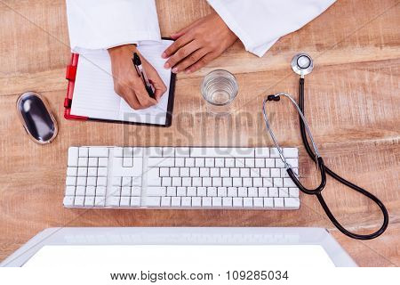 Doctor writing on her diary on desk