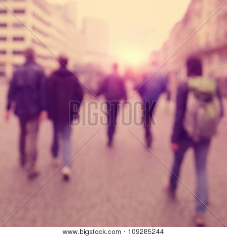 Abstract image of blurred people on the street at sunset.