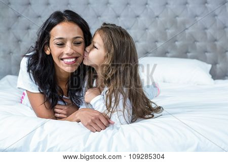Cute child kissing her mother on the bed at home