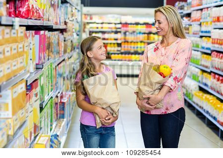 Smiling mother and daughter with grocery bags at the supermarket