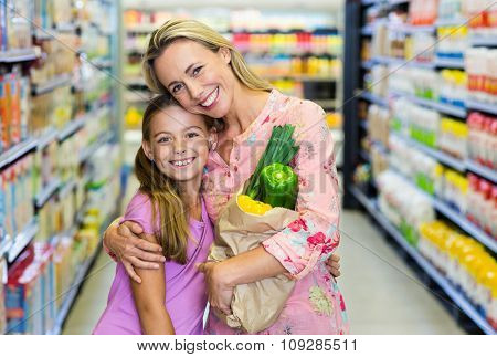 Smiling mother and daughter with grocery bag at the supermarket